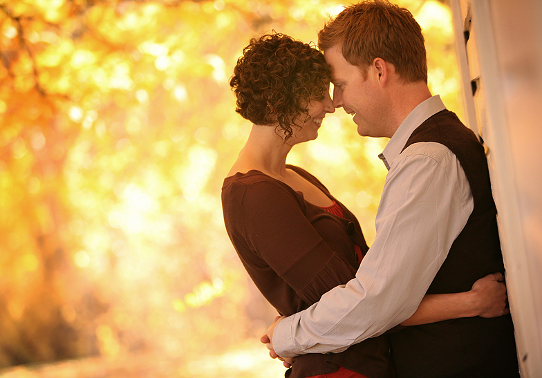 engaged couple embracing against a wall with orange yellow leaves in the background