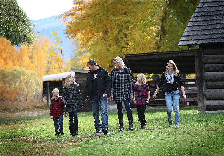 family of 6 wearing dark colours walking in a line in a farm yard with fall leaves