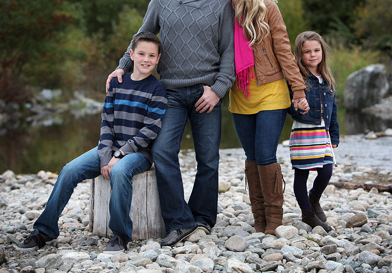 family of 4 standing on a rocky beach, cropped out parents with focus on kids in stripped outfits