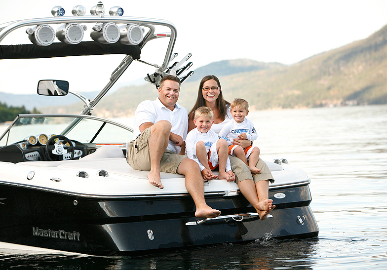 family of 4 wearing white t-shirts sitting on a boat on the lake by mountains