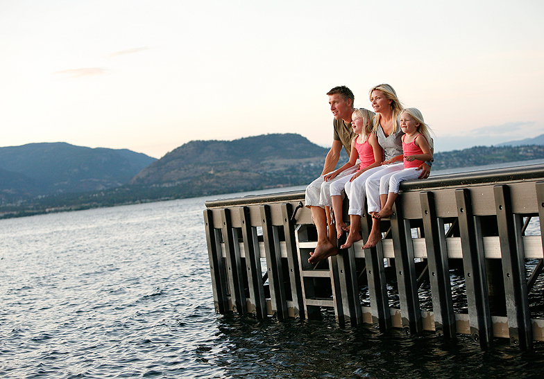 family of 4 wearing white pants, girls wearing coral shirts, sitting on a dock by the lake and mountains