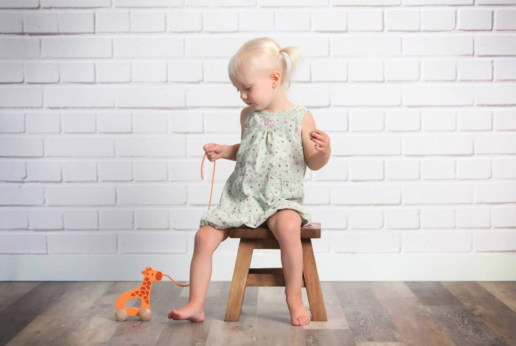 Young girl with blond pig-tails wearing a green dress playing with an orange toy sitting on a stool infant of white brick