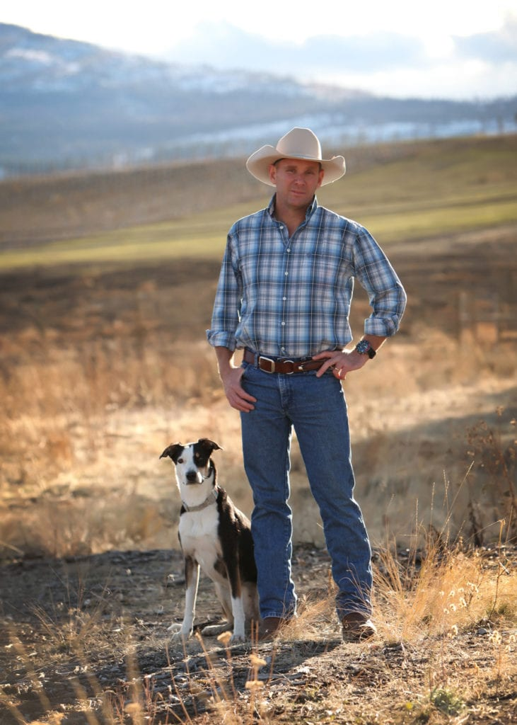 Business Portrait of a man wearing blue plaid and a white cowboy hat standing in a field of dried grass and mountains with dog