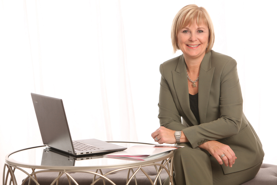 Business Portrait of a blond woman wearing an olive suit sitting by a table with laptop in front of white curtains