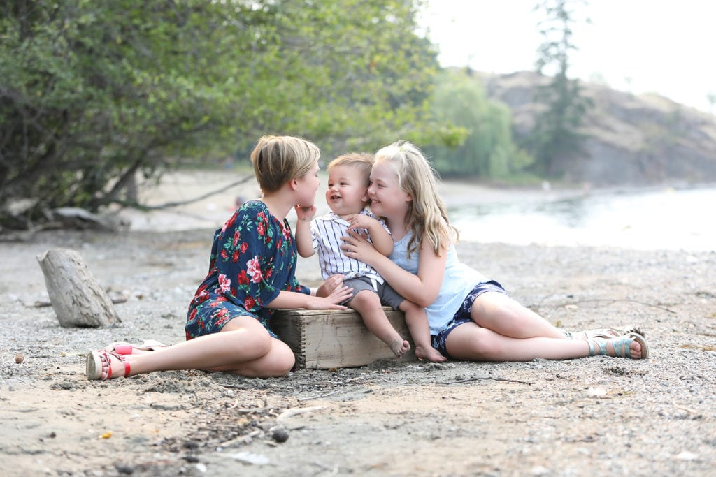 3 siblings sitting and laughing on a beach
