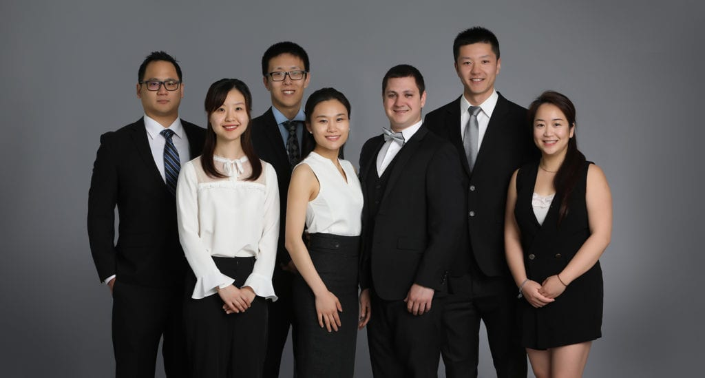Business Portrait of a group of people wearing black suits and white shirts against a grey backdrop