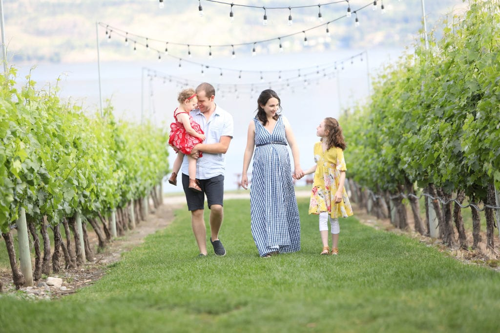 Maternity Portrait of a family wearing red, blue and yellow walking down a Okanagan vineyard row with string lights