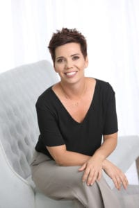 Business Portrait of a black short haired woman wearing a black shirt and grey pants sitting on a grey bench in front of white curtains