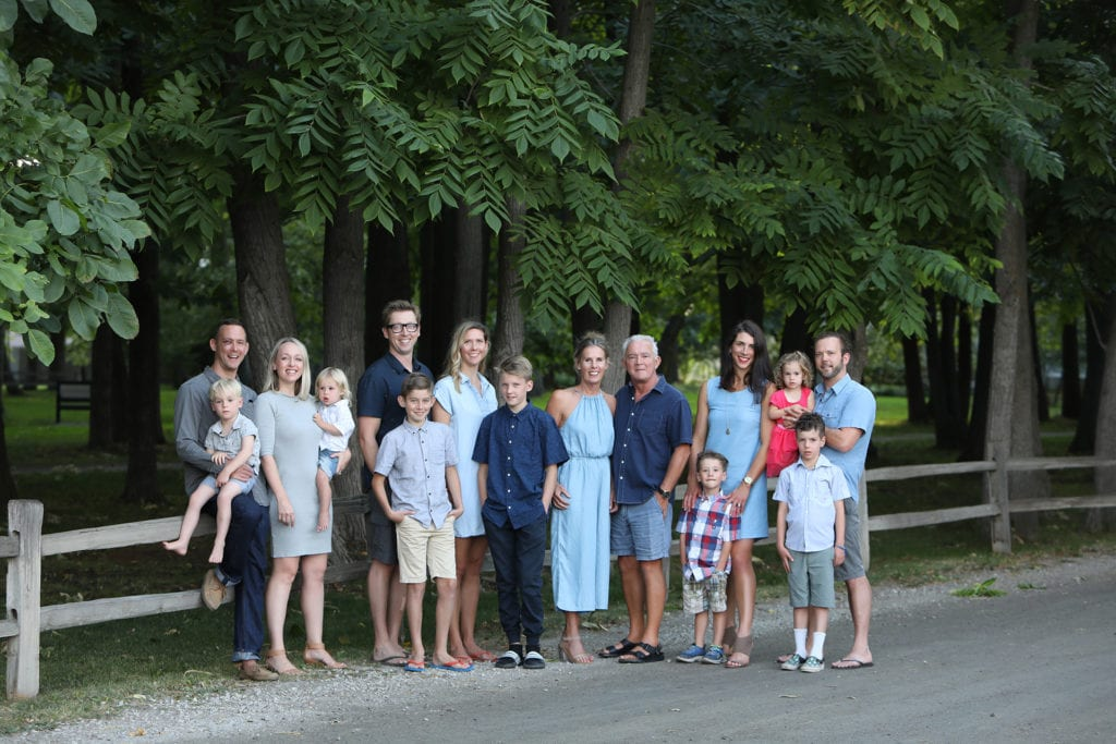 large family portrait standing by a rustic fence by a road and forest one child wears a red dress