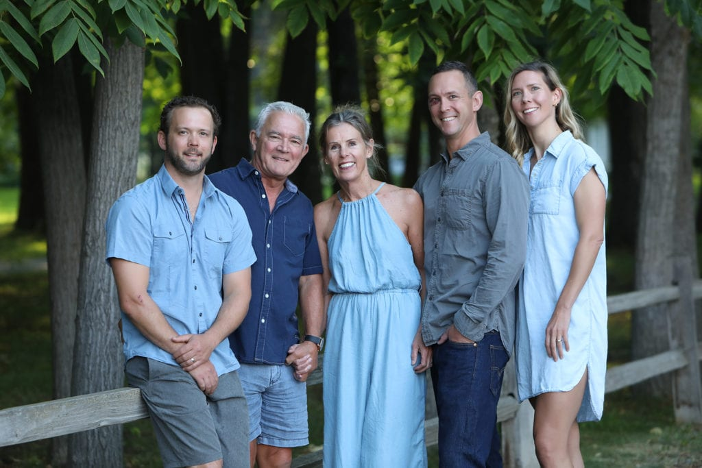 family of 5 wearing grey and blue stand and sit by a rustic fence by forest