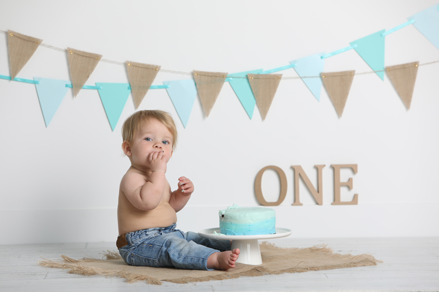 one year old boy wearing jeans and eating cake on a burlap mat in front of aqua coloured pennants