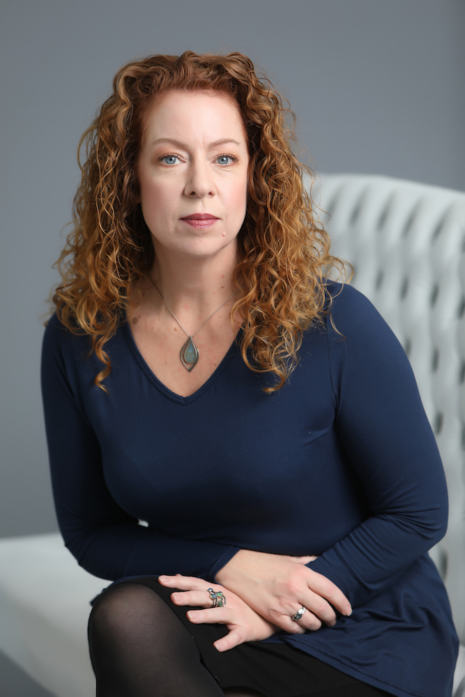 business headshot portrait of a curly red haired woman wearing a black shirt and sitting on a grey bench against a grey background